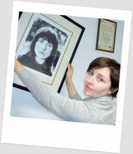 Chairman Aoife NicFhearghusa hangs up a portrait of poet Chaitlín Maude in the new offices - LitPix 2011